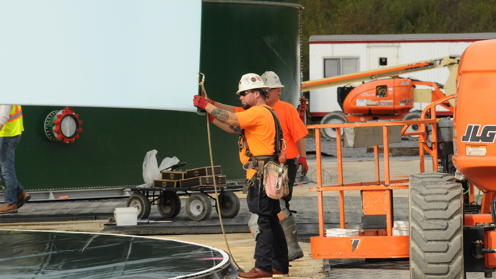 Comtech workers in Coudersport, PA; workers wearing bright clothing, orange, yellow vest; holding big piece of DYNA Tank
