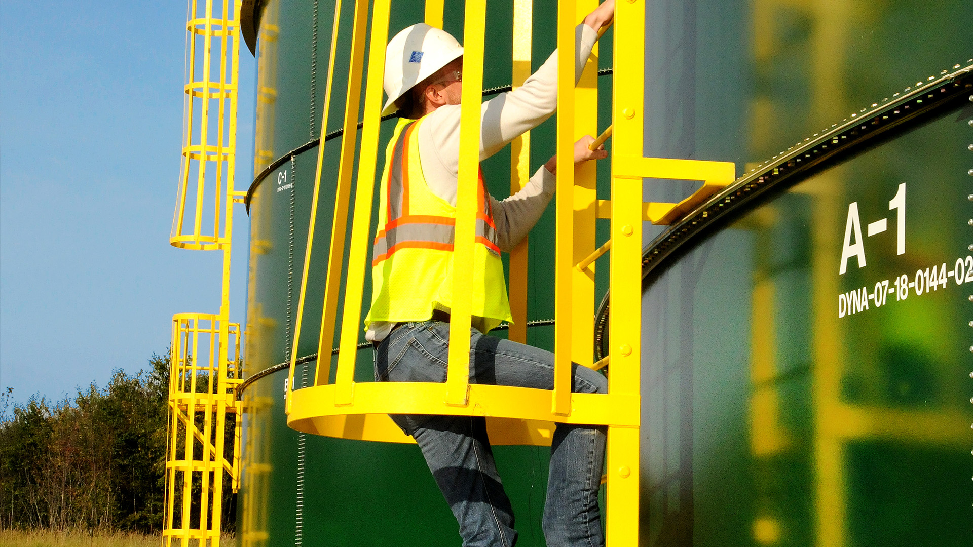water storage tank worker climbing ladder, wearing bright green vest and white hard hat and safety goggles, bright yellow ladder on green tank